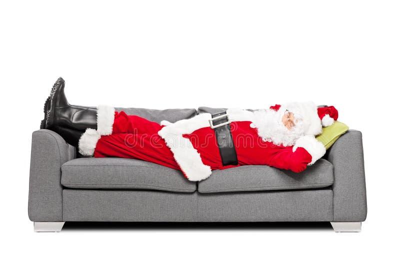 睡觉在一个现代沙发的圣诞老人 免版税库存照片