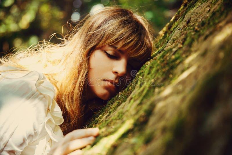 睡觉在一块石头的美丽的长发女孩在山的一个森林里 童话 库存图片
