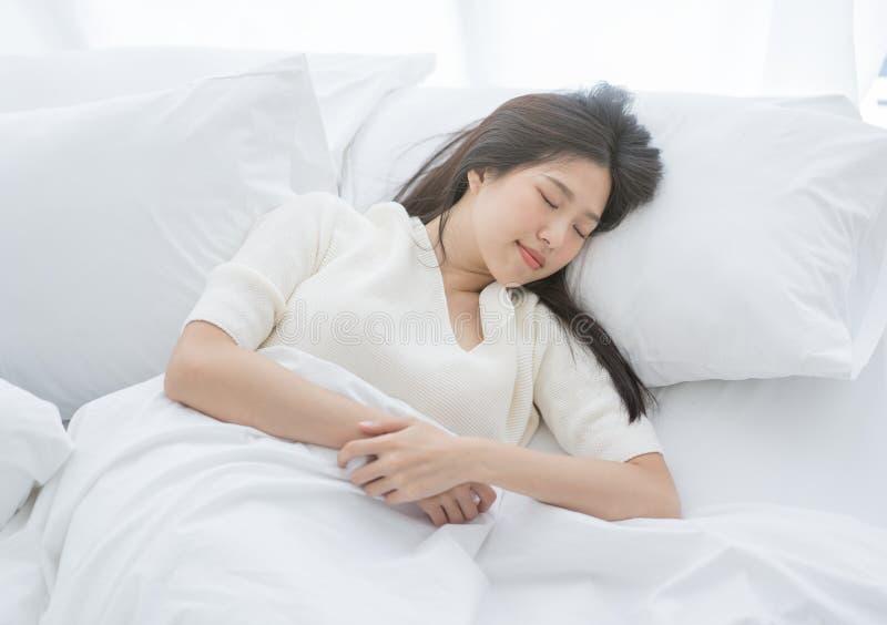 睡觉在一张白色床上的年轻亚裔妇女在清早 免版税库存图片