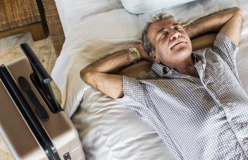 睡觉在一张白色床上的老人 免版税库存图片