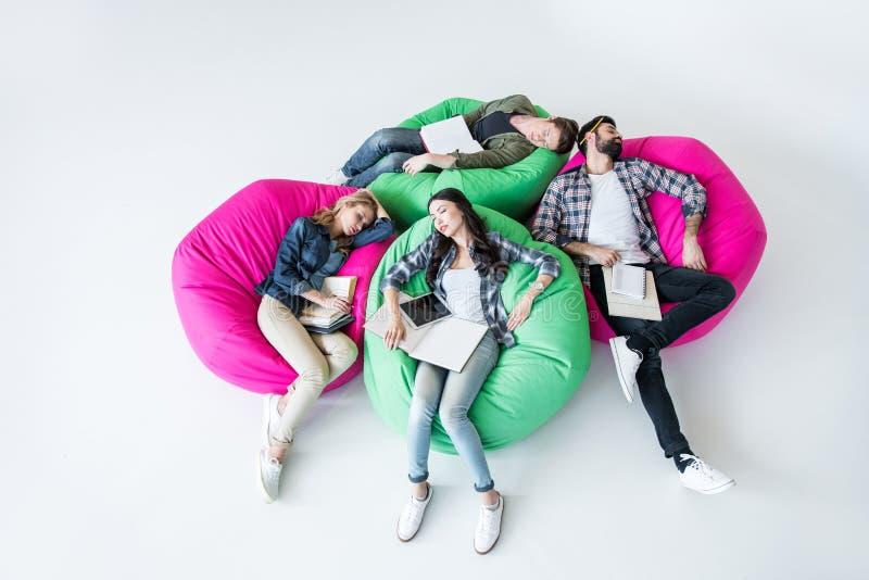 睡觉在与书的装豆子小布袋椅子的疲乏的学生在演播室 库存图片
