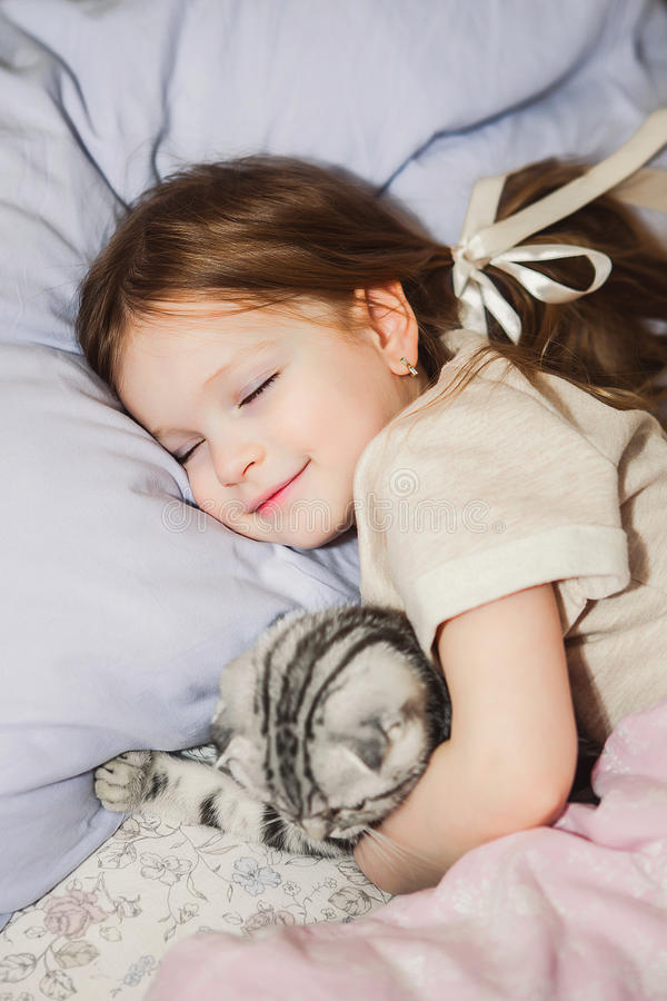 睡觉在与她的猫的床上的小女孩 图库摄影