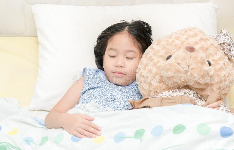 睡觉在与她的玩具熊的床上的可爱的小女孩 图库摄影