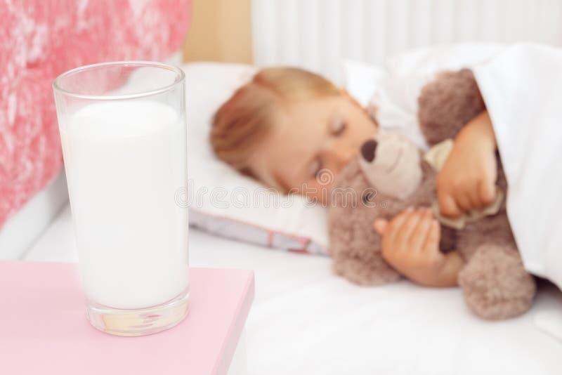 睡觉在与她的玩具熊的床上的小女孩 免版税库存照片