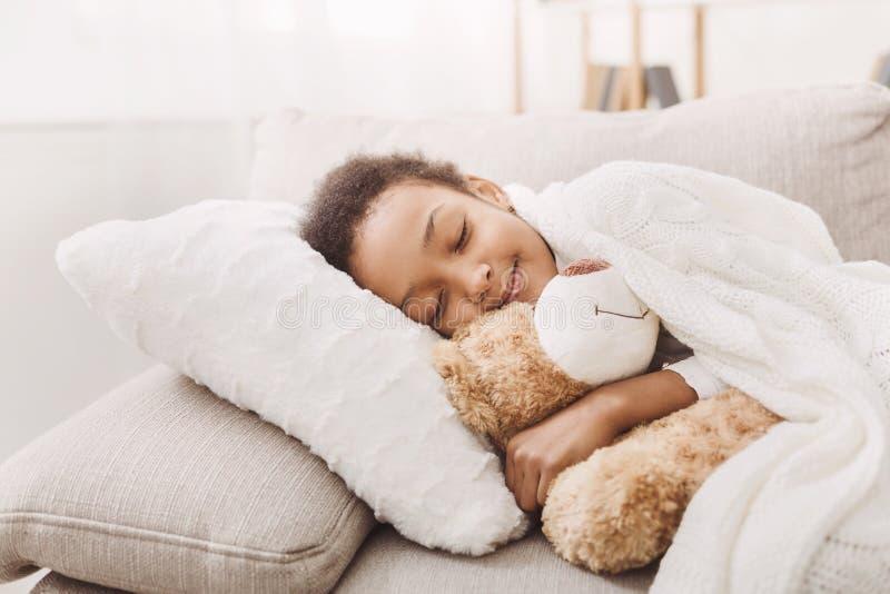 睡觉在与她的玩具的床上的可爱的女孩 免版税库存照片