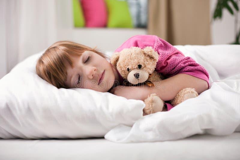 睡觉在与她的玩具的床上的可爱的小女孩 库存照片