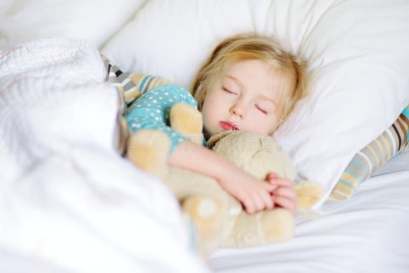 睡觉在与她的玩具的床上的可爱的小女孩 免版税库存图片