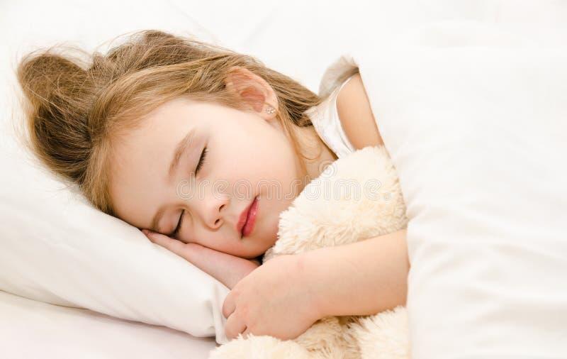 睡觉在与她的玩具的床上的小女孩 库存图片