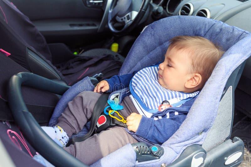 睡觉在与安全带锁着的保护的汽车座位的小孩子 免版税库存图片