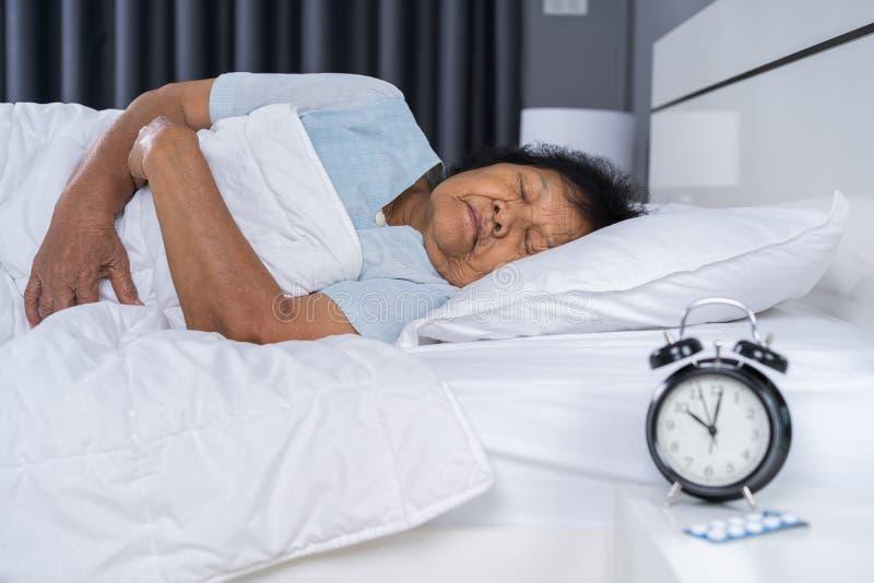 睡觉在与时钟的一张床上的资深妇女 库存照片