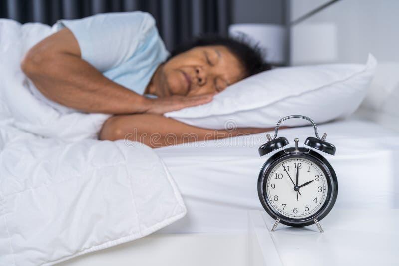 睡觉在与时钟的床上的资深妇女 库存照片