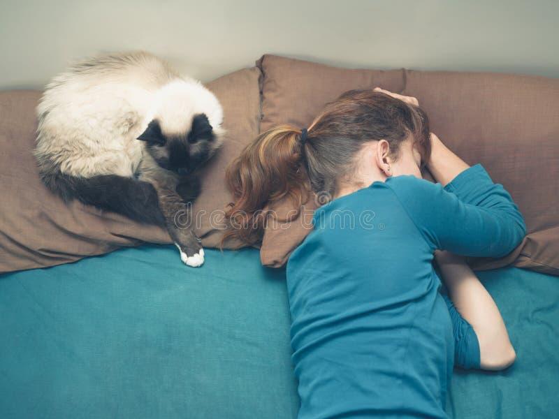 睡觉在与猫的床上的妇女 免版税库存图片