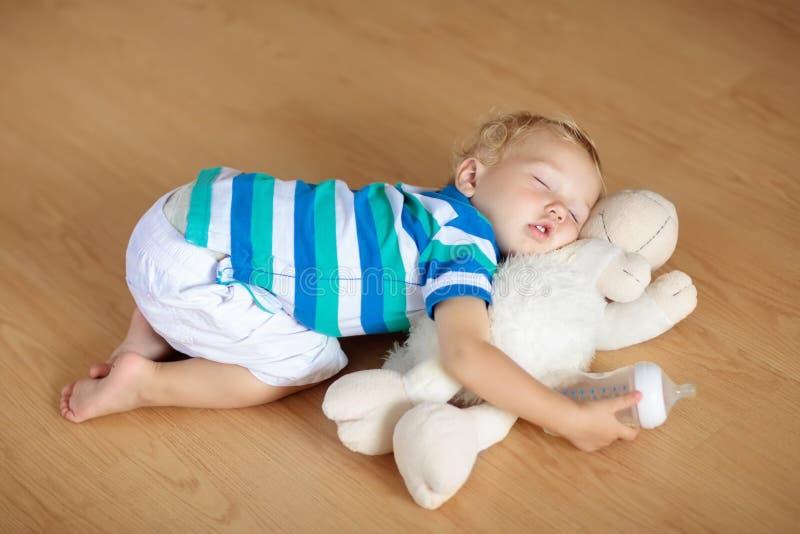 睡觉在与玩具和牛奶瓶的地板上的婴孩 免版税库存照片