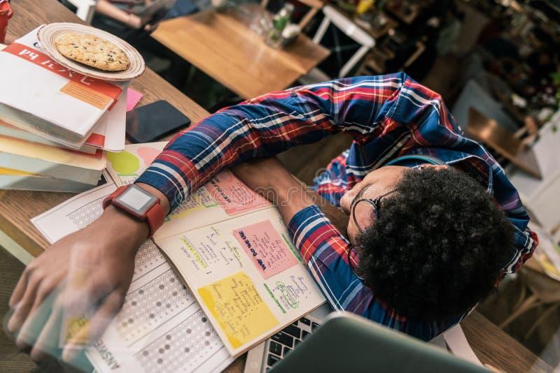 睡觉在书桌上的宜人的年轻人 免版税图库摄影