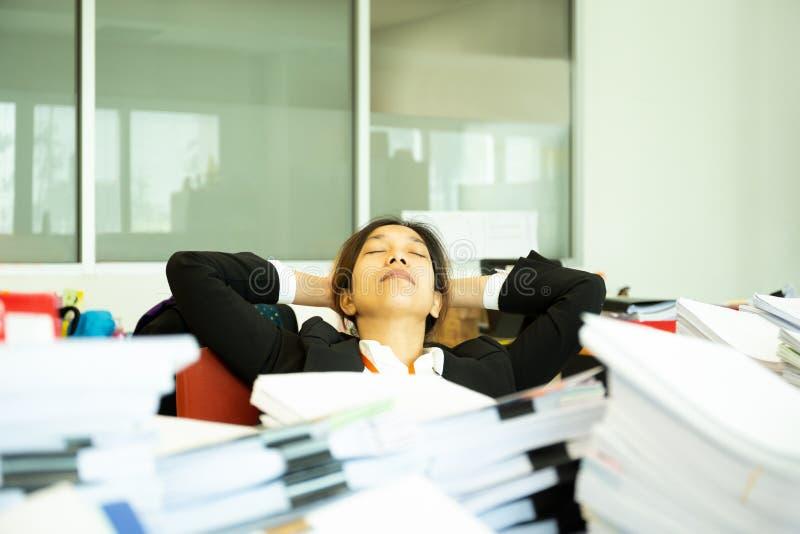 睡觉在书桌上的被用尽的女实业家在有堆的办公室paperwok 图库摄影