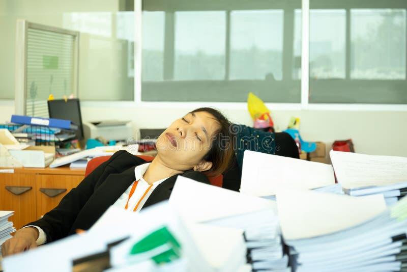 睡觉在书桌上的被用尽的女实业家在有堆的办公室paperwok 免版税库存照片