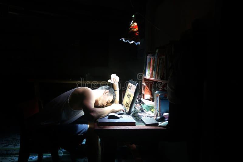 睡觉在书桌和一台计算机上的亚裔人在房子里 库存照片