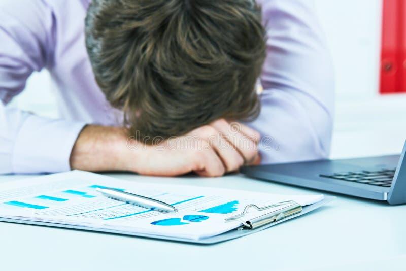 睡觉在书桌的一台膝上型计算机的疲乏的劳累过度的年轻商人在工作在他的办公室 免版税库存图片