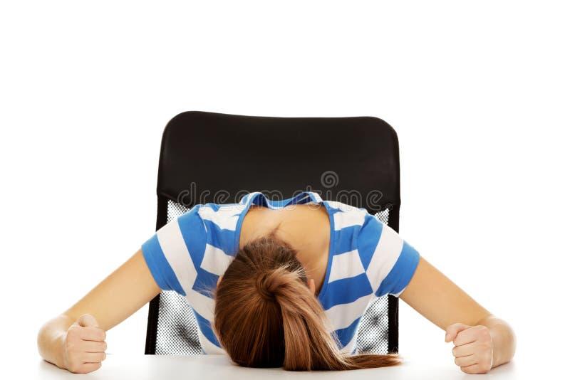 睡觉在书桌的担心的少年妇女 库存照片