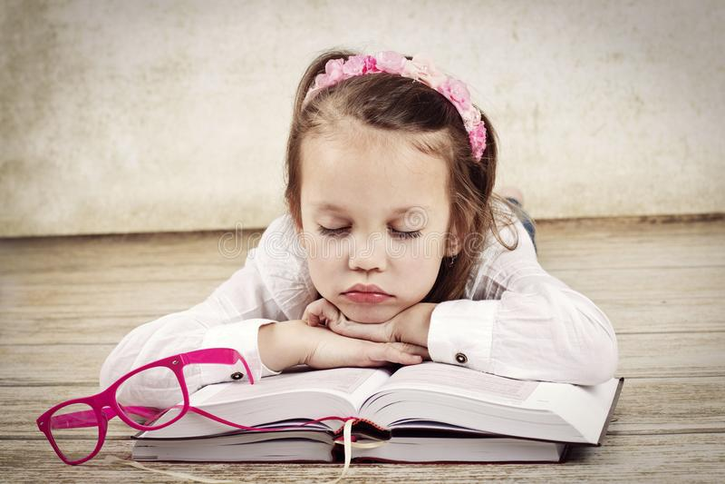 睡觉在书的小疲乏的女孩 免版税库存照片