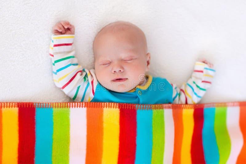 睡觉在五颜六色的毯子下的小男婴 免版税库存图片