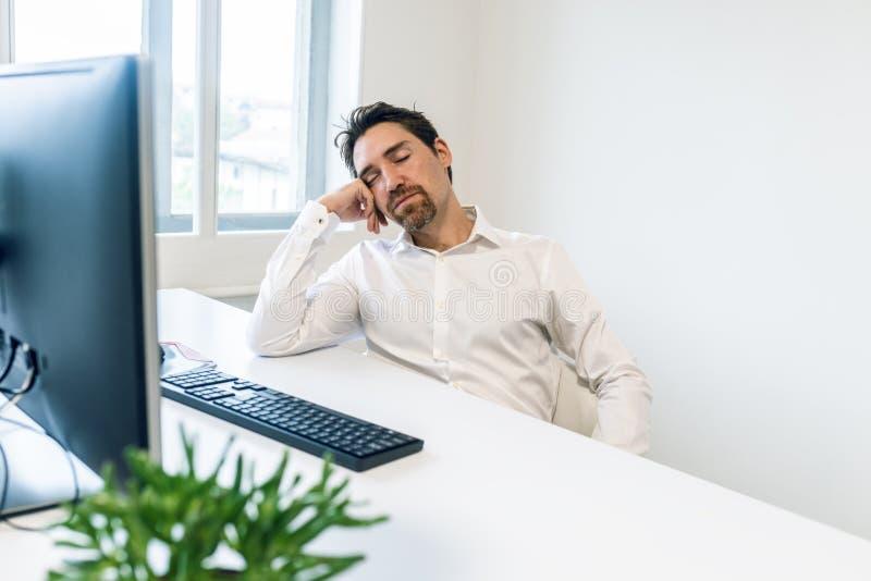 睡觉在他的书桌的劳累过度的年轻商人 免版税库存图片