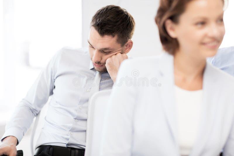 睡觉在会议的疲乏的商人 库存图片