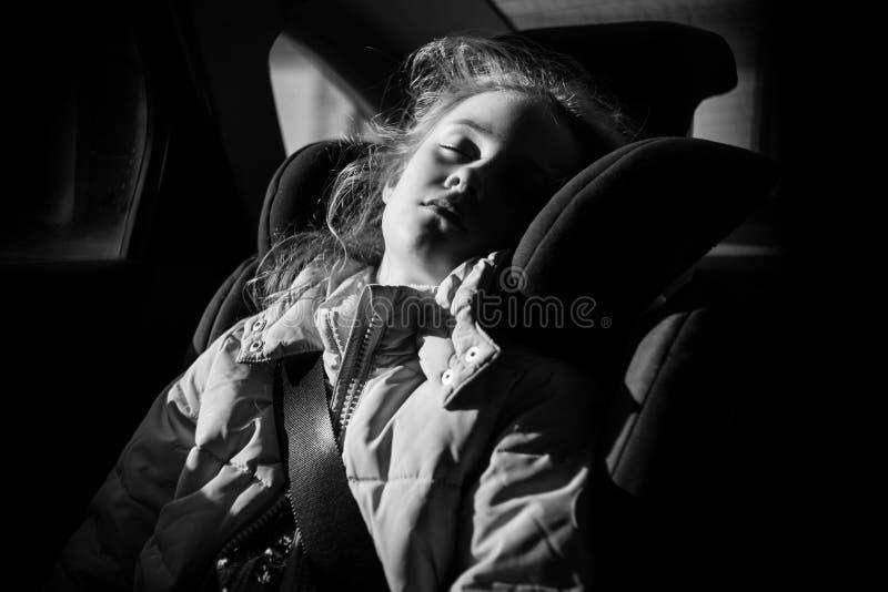 睡觉在儿童汽车座椅的七年迷人的女孩 免版税库存照片