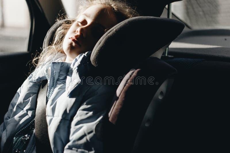 睡觉在儿童汽车座椅的七年迷人的女孩 库存照片