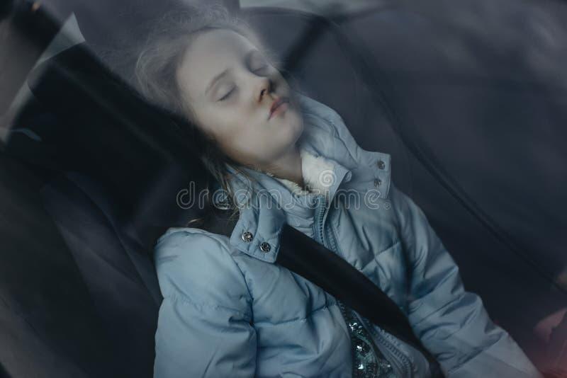 睡觉在儿童汽车座椅的七年迷人的女孩 免版税库存图片