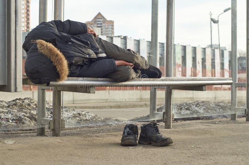 睡觉在公共汽车站的醉酒的叫化子 免版税库存照片