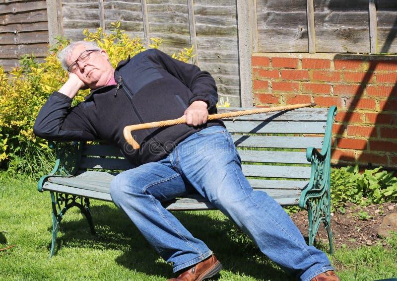 睡觉在公园长椅的老人 免版税库存照片