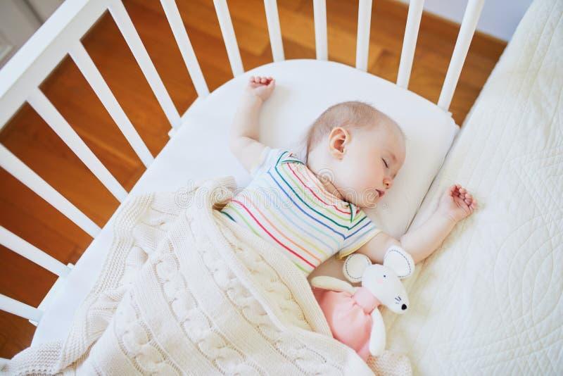 睡觉在共同睡眠者小儿床的女婴 免版税库存照片