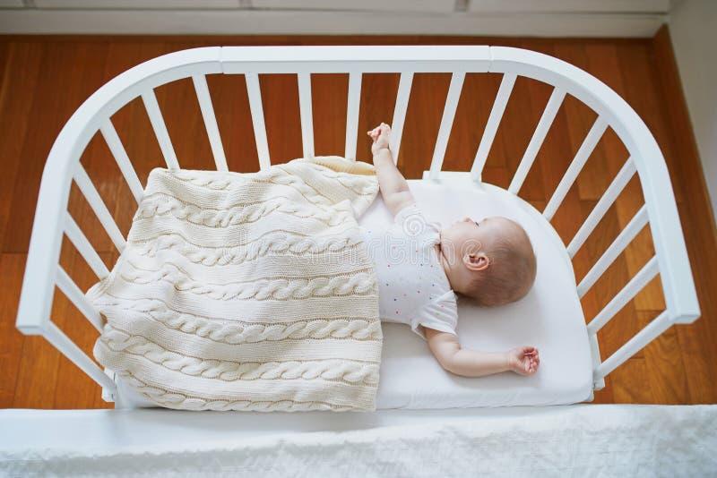 睡觉在共同睡眠者小儿床的女婴 免版税库存图片