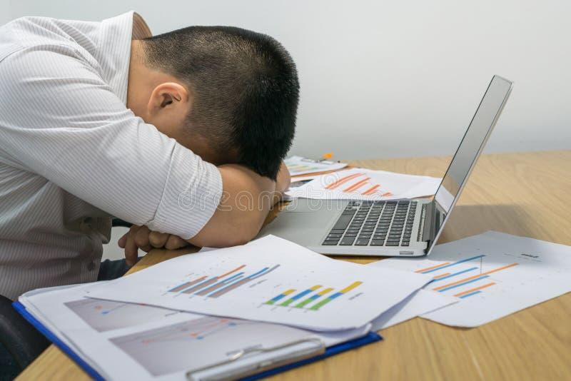 睡觉在办公室的年轻疲乏的商人 库存照片