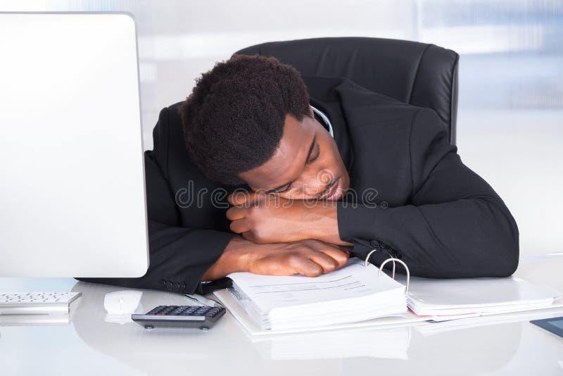 睡觉在办公室的被注重的商人 免版税库存图片