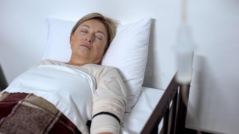 睡觉在医院病床上的微弱的领抚恤金者患者在下落逆治疗下 库存照片