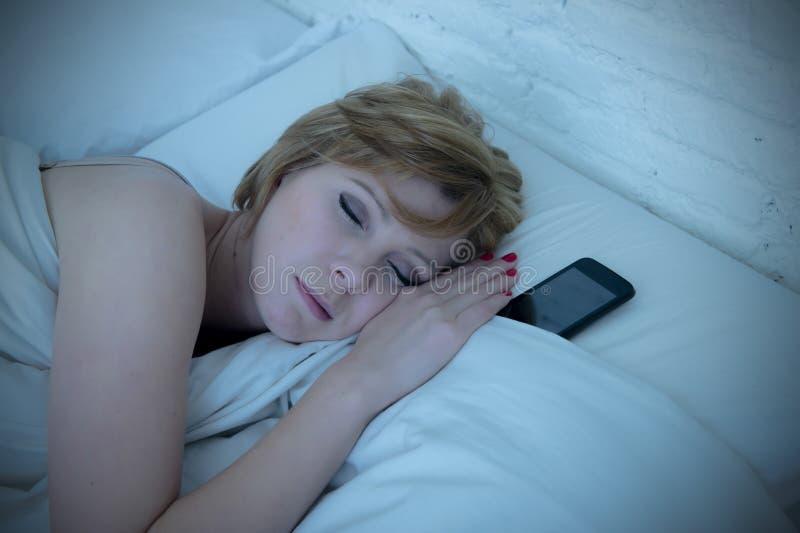 睡觉在单独床上的年轻可爱的妇女拿着手机在她旁边在晚上作为上瘾者 图库摄影