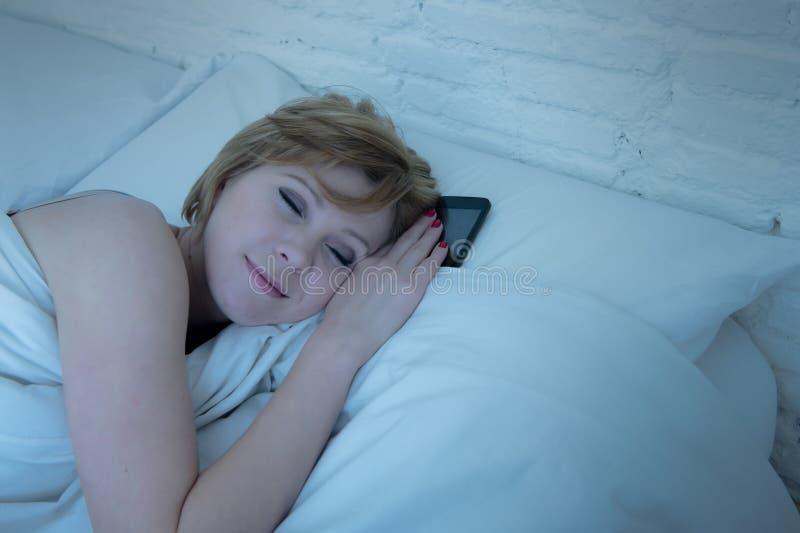 睡觉在单独床上的年轻可爱的妇女拿着手机在她旁边在晚上作为上瘾者 库存照片