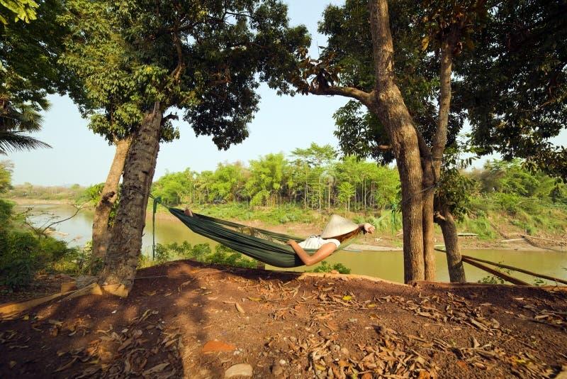睡觉在吊床,琅勃拉邦,老挝的旅游女孩 免版税库存照片