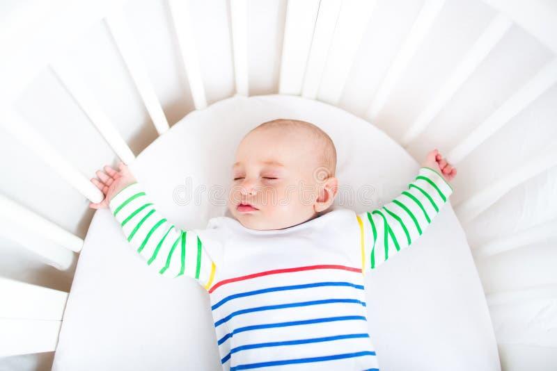 睡觉在圆的小儿床的逗人喜爱的新出生的小男孩 免版税库存图片