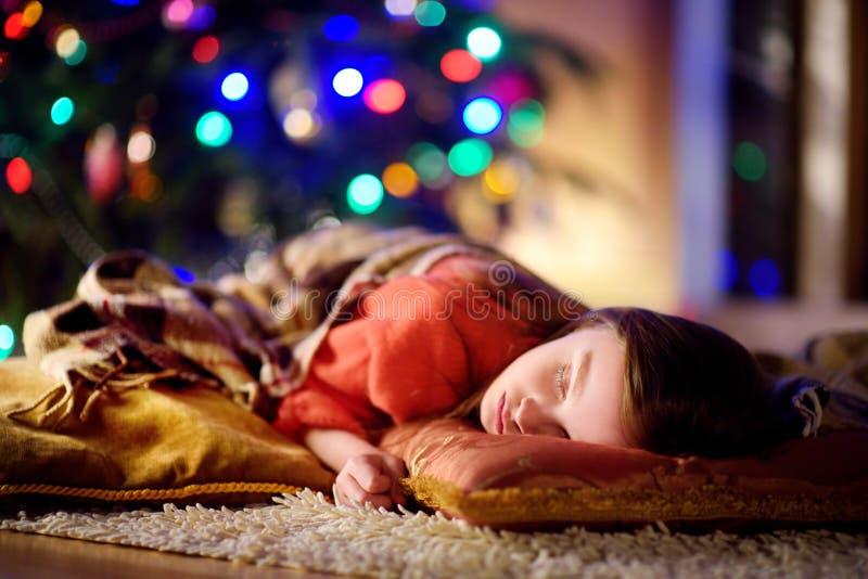 睡觉在圣诞树下的可爱的小女孩由壁炉 免版税库存图片
