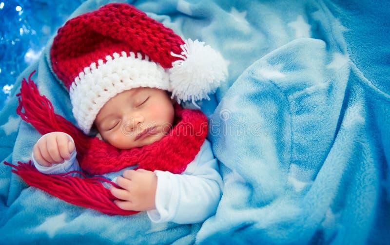 睡觉在圣诞老人帽子的逗人喜爱的男婴 免版税库存照片