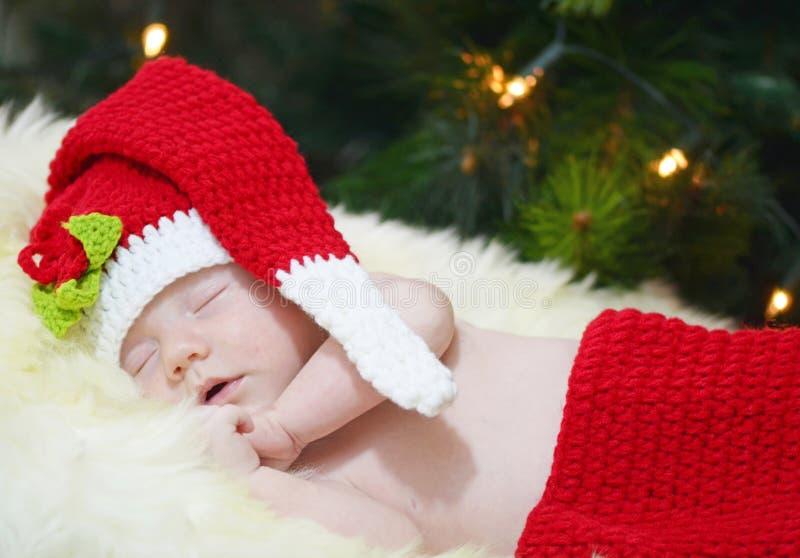 睡觉在圣诞节在白色毛皮地毯的编织服装的新出生的婴孩画象 图库摄影