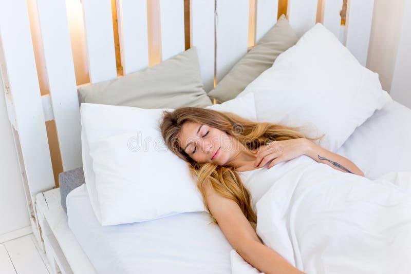 睡觉在她床和放松上的年轻美丽的妇女 免版税图库摄影