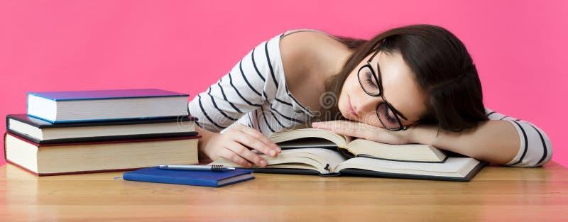 睡觉在她的书桌的被用尽的学生 库存照片
