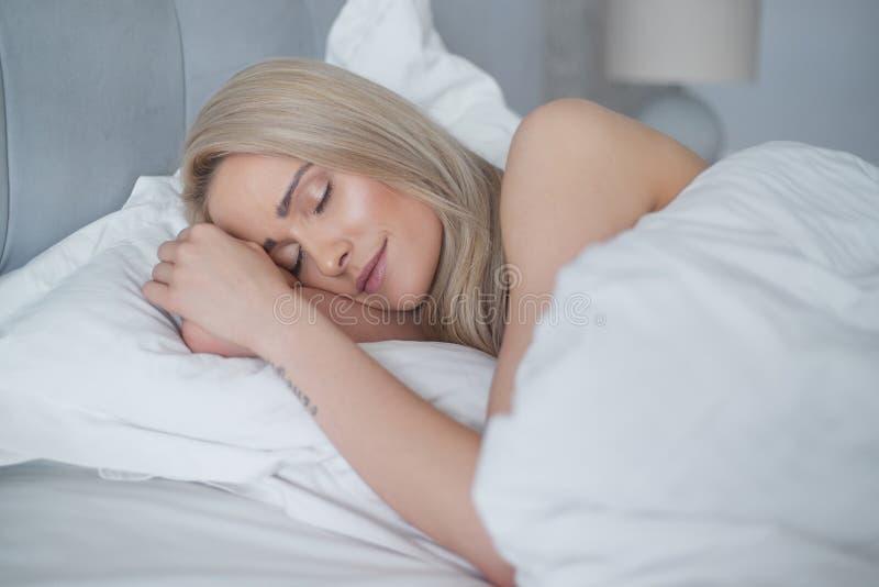 睡觉在她的卧室的年轻美丽的白肤金发的妇女 库存图片
