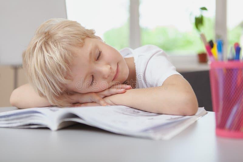睡觉在她的家庭作业的可爱的矮小的女小学生 图库摄影