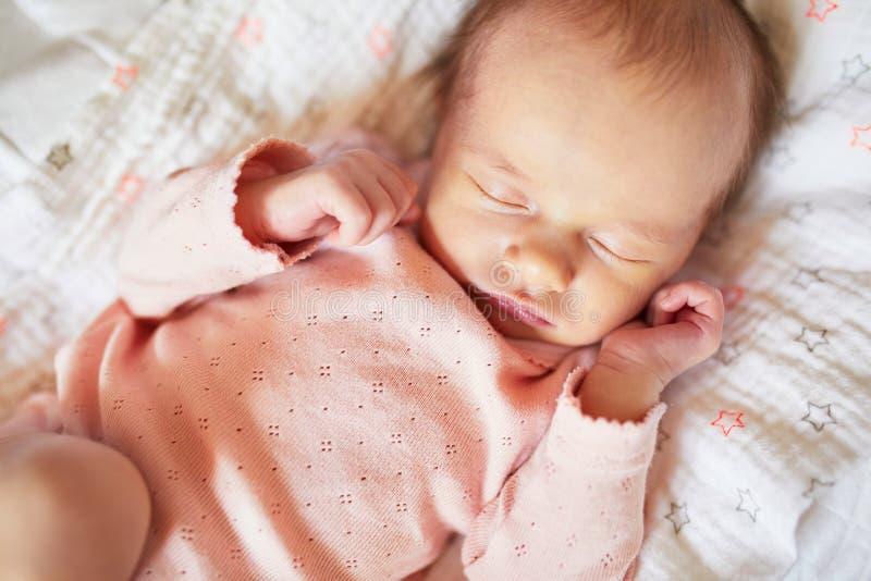 睡觉在她的小儿床的新出生的女婴 免版税库存照片