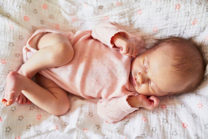 睡觉在她的小儿床的新出生的女婴 免版税图库摄影
